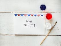 Card with a pattern of the US Flag. Handwritten inscription with congratulations on July 4th on a white, vintage, wooden table. Top view, close-up. Concept of Stock Photo