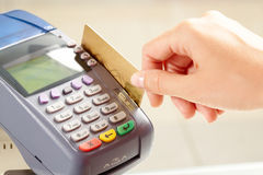 Card payment. Close-up of payment machine buttons with human hand holding plastic card near by Stock Photos