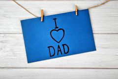 Card with phrase I LOVE DAD for Father`s Day. Hanging on string against wooden background Stock Photography