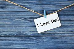 Card with phrase I LOVE DAD for Father`s Day. Card with phrase I LOVE DAD for Father's Day hanging on string against wooden background Royalty Free Stock Images