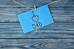 Card with phrase I LOVE DAD for Father`s Day. Hanging on string against wooden background Stock Photo