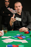 Card player throwing in his hand Stock Images