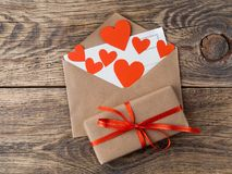 Card and red hearts in open envelope from brown Kraft paper. Gif Stock Photography
