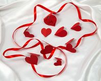 Card, red satin ribbon in the texture with the cardboard red hearts. On white fabric stock images