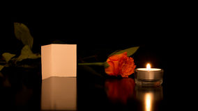 Card with Rose and Candle on Shiny Black Surface Royalty Free Stock Photo