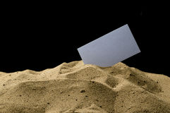 Card in the sand. On a black background Royalty Free Stock Photography
