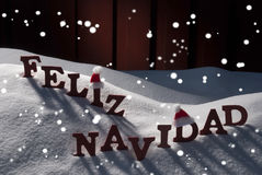Card With Santa Hat, Snowflakes, Feliz Navidad Mean Christmas. Red Letters With Santa Hat On White Snow With Snowflakes As Christmas Card.  Spanish Text Or Word Royalty Free Stock Photography
