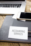 Card saying Accounting Services on note pad. At desktop in office with laptop, tablet computer and phone Royalty Free Stock Images