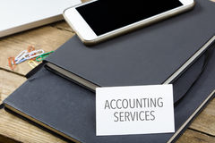 Card saying Accounting Services on note pad. At desktop in office with laptop, tablet computer and phone Royalty Free Stock Photos