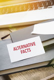 Card saying Alternative Facts on note pad. At desktop in office with laptop, tablet computer and phone stock image