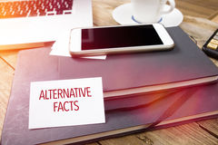 Card saying Alternative Facts on note pad. At desktop in office with laptop, tablet computer and phone royalty free stock photos