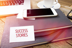 Card saying Success Stories on note pad. At desktop in office with laptop, tablet computer and phone Royalty Free Stock Photos