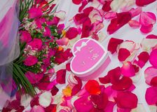 Card. Set on a leaf with rose petals - a bouquet of roses and a box in the form of a heart with a gift. stock image