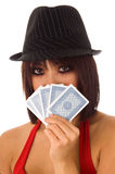 Card Shark. Close-up head shot of a beautiful young Asian model playing poker and hiding her face behind her cards Royalty Free Stock Image