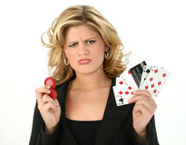 Card Shark. Upset young woman with bad poker hand and credit card.  Poker chips in other hand Royalty Free Stock Image