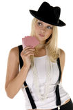 Card Shark. Young blonde woman in suspenders and a fedora playing her cards close to her chest Royalty Free Stock Image
