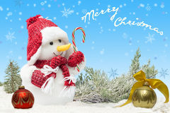 Card with Snowman  in red hat and scarf  near fir balls on blue background and falling snowflakes. Royalty Free Stock Photo