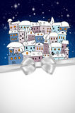 Card with snowy village under night sky and silver bow Stock Images