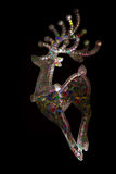 Card with stylized abstract many-colored deer on black background. Royalty Free Stock Images