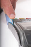 Card Swipe. Macro / close up image of a credit card being swiped through a card machine. Focus is on the finger and front edge of the credit card Royalty Free Stock Images