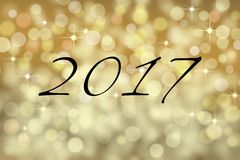 2017 text card and gold bokeh backgound. New years card with gold sparkle bokeh backgound with number 2017 stock photo