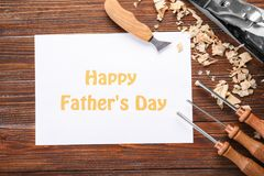 Card with text Happy Father`s Day and carpenter`s tools. On wooden table Stock Images