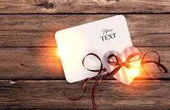 Card for text and heart with ribbon on wooden background. Royalty Free Stock Photography