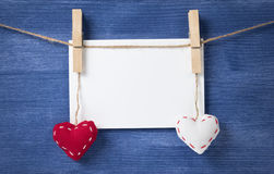 Card and textile hearts over wooden wall Stock Image