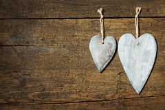 Card with two wooden hearts on aged wooden background Stock Images