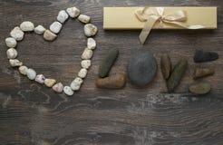 Card valentin, förälskelseordet som göras av stenar Arkivbild