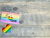 Card on which is written love is love with a rainbow background and a heart with the LGBT flag lie on a light blue textured wooden. Board, has free space to stock photos