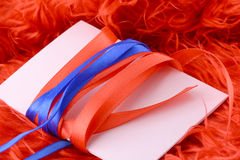 Card with white paper with blue and red bow Stock Image