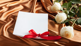 Card with white roses on golden silk background. For text Royalty Free Stock Photography