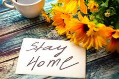 Free Card With Message Stay Home And Bright Yellow Flowers On Wooden Background. Royalty Free Stock Photo - 178828895