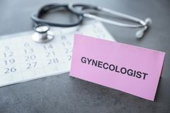 Card with word Gynecologist near calendar on table. Card with word Gynecologist near calendar and stethoscope on table royalty free stock images