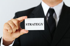 Card with word Strategy. Businessman holding card with word Strategy Stock Image