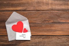 Card with words HAPPY FATHER`S DAY,. Envelope and paper hearts on wooden background, top view Royalty Free Stock Images