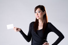 A Card for You. Young Professional woman holding and showing a white Card while  smiling Royalty Free Stock Photography