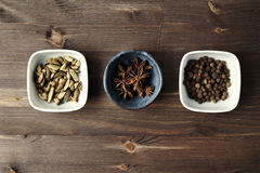 Cardamom, anise, allspice in ceramics bowls on wooden table. Cui Stock Photos