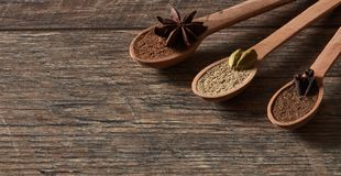 Cardamom, cloves, star anise. Ground spices in wooden spoons.Different types of whole Indian spices in wooden background royalty free stock photo
