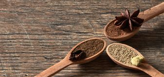 Cardamom, cloves, star anise. Ground spices in wooden spoons.Different types of whole Indian spices in wooden background stock photography