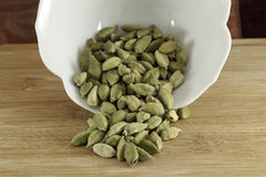 Cardamom Green Seeds. Cardamom whole green seeds spilling out of a bowl Royalty Free Stock Images