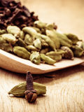 Cardamom pods and cloves on wooden spoon Stock Photo