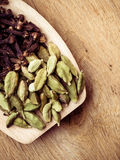 Cardamom pods and cloves on wooden spoon Stock Photos