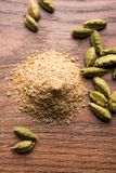 Cardamom powder or elaichi powder in bowl over moody background with pods. Elaichi or Cardamom powder in bowl or heap over moody background with pods. selective Royalty Free Stock Photos