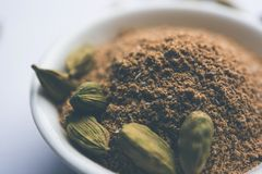 Cardamom powder or elaichi powder in bowl over moody background with pods. Elaichi or Cardamom powder in bowl or heap over moody background with pods. selective Royalty Free Stock Photo