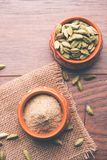 Cardamom powder or elaichi powder in bowl over moody background with pods. Elaichi or Cardamom powder in bowl or heap over moody background with pods. selective Stock Photography