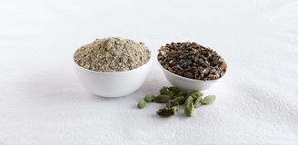 Cardamom Powder and Seeds in Bowls. Cardamom powder, which is used as a flavoring ingredient particularly in some sweet dishes and in some drinks, and seeds royalty free stock photos