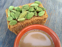 Cardamom and rusk and tea. Placed on wooden board stock photos
