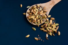 Cardamom seeds in wooden spoon on blue backgro Royalty Free Stock Photos